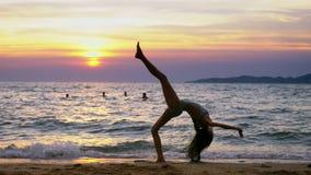 Silhueta de uma menina no por do sol, na perspectiva do mar, golpe ginásticos fazendo engraçados da menina pernudo delgada no filme