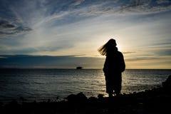 Silhueta de uma menina que está apenas no litoral com o céu bonito no fundo fotos de stock royalty free