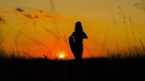 Silhueta de uma menina que faz a ioga no por do sol video estoque