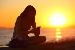 Silhueta de uma menina que usa um telefone esperto no por do sol imagem de stock royalty free