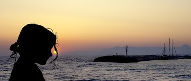 Silhueta de uma moça com por do sol sobre em Gouves, Creta fotos de stock royalty free