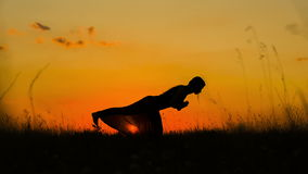 Silhueta de uma moça que faz a ioga no por do sol video estoque