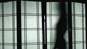 Silhueta de uma mulher que dance para o vidro translúcido video estoque