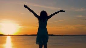 A silhueta de uma mulher que enfrenta The Sun levanta suas mãos acima no por do sol vídeos de arquivo