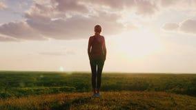 Silhueta de uma mulher que está em uma parte superior do monte que enfrenta o sol Contra um fundo de um vale muito bonito Vista t filme