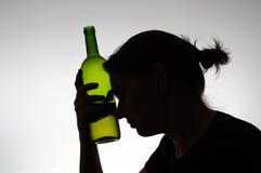 Silhueta de uma mulher que guarda uma garrafa Imagens de Stock Royalty Free