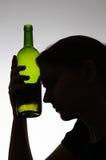 Silhueta de uma mulher que guarda uma garrafa Foto de Stock Royalty Free