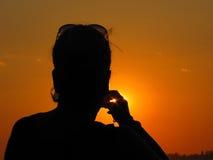 Silhueta de uma mulher que toma a foto do por do sol Fotografia de Stock