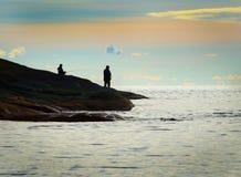 Silhueta de uma pesca de dois homens Imagem de Stock Royalty Free