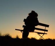 Silhueta de uma pessoa que senta-se em um banco no por do sol imagem de stock royalty free