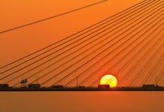 Silhueta de uma ponte sob o sol de ajuste fotografia de stock royalty free