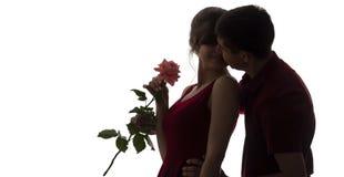 A silhueta de uma queda do homem novo e da mulher no amor no fundo isolado branco, menino veio acima atrás à menina fazer uma sur fotos de stock