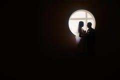 Silhueta de uns noivos no fundo da janela Imagens de Stock
