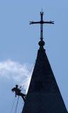 A silhueta do alpinist limpa o telhado da igreja Imagem de Stock Royalty Free