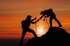 Silhueta do amigo de ajuda do amigo que escala acima a montanha dando uma mão foto de stock royalty free