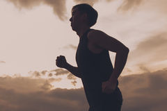 Silhueta do atleta do corredor que corre em público o parque conceito movimentando-se do bem-estar do exercício do nascer do sol  Fotografia de Stock