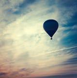 Silhueta do balão de ar quente no por do sol Imagem de Stock