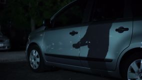 A silhueta do bandido com bastão entrega a espera no estacionamento da noite, atividade criminal video estoque
