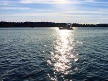 Silhueta do barco na água com reflexão de Sun Fotos de Stock