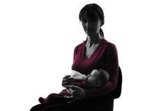 Silhueta do bebê de garrafa da alimentação da mulher Fotos de Stock