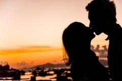 Silhueta do beijo dos pares na praia no nascer do sol e no por do sol Fotografia de Stock
