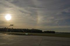 Silhueta do biplano aproximadamente à terra durante o por do sol Imagens de Stock