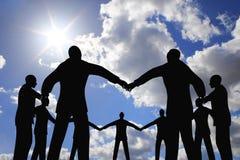 Silhueta do círculo do grupo dos povos na colagem do céu do sol Fotografia de Stock Royalty Free
