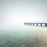 Silhueta do cais ou do molhe em um lago nevoento. Lago Garda, Italia foto de stock