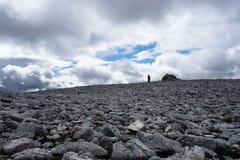 Silhueta do caminhante no campo da rocha em montanhas escocesas Munro Foto de Stock