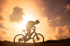 A silhueta do cavaleiro da bicicleta da montanha no monte Imagens de Stock