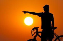 Silhueta do cavaleiro da bicicleta no por do sol Imagens de Stock