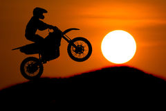 A silhueta do cavaleiro do velomotor salta a inclinação transversal da montanha com Fotografia de Stock Royalty Free