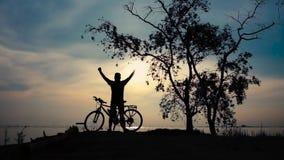Silhueta do ciclista que anda com a bicicleta no beira-mar, esticando o exercício video estoque