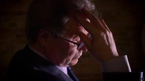 Silhueta do close-up do homem de negócios dos relógios do leanin superior pensativamente disponível que está na escuridão complet vídeos de arquivo