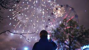 A silhueta do close up do homem que olha e que fotografa fogos-de-artifício explode na câmera do smartphone fora fotos de stock royalty free