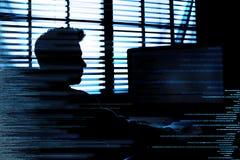 Silhueta do computador de corte criminoso do cyber atrás dos símbolos digitais fotos de stock royalty free