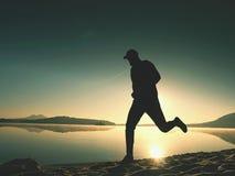 Silhueta do corredor atlético que movimenta-se na praia contra o nascer do sol fotos de stock royalty free