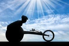 A silhueta do desportista desabilitou em uma cadeira de rodas de competência imagem de stock