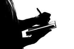 Silhueta do diário do negócio da escrita do homem Imagem de Stock