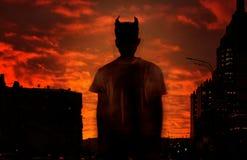Silhueta do diabo no fundo do céu ensanguentado vermelho fotografia de stock royalty free