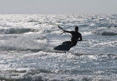 A silhueta do embarque do papagaio do homem novo no mar acena Imagens de Stock Royalty Free