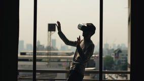 A silhueta do filme de observação do homem novo em auriculares de VR e tem a experiência da realidade virtual no balcão da sala d Imagens de Stock Royalty Free