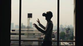 A silhueta do filme de observação do homem novo em auriculares de VR e tem a experiência da realidade virtual no balcão da sala d Imagens de Stock