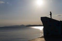 Silhueta do fisheman com a vara de pesca na luz da tarde imagens de stock royalty free