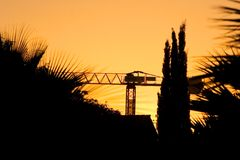 Silhueta do guindaste e das árvores durante um por do sol Fotos de Stock Royalty Free