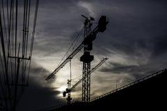 Silhueta do guindaste na construção com céu do por do sol Foto de Stock Royalty Free