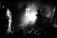 Silhueta do guitarrista na ação na fase Fotografia de Stock Royalty Free