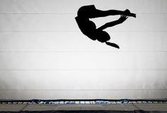 Silhueta do gymnast no trampoline foto de stock