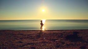 Silhueta do homem ativo do esporte que corre e que exercita na praia no por do sol filme
