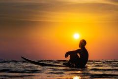 A silhueta do homem da ressaca senta-se em uma prancha Surfar no por do sol Fotografia de Stock